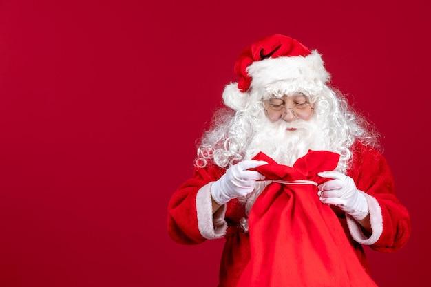 Vooraanzicht kerstman die zak vol cadeautjes opent voor kinderen op een rode feestdag