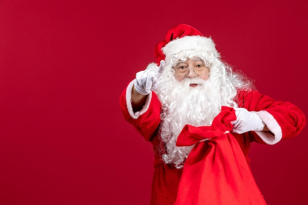 Vooraanzicht kerstman die zak vol cadeautjes voor kinderen opent op rode kerstmisemoties