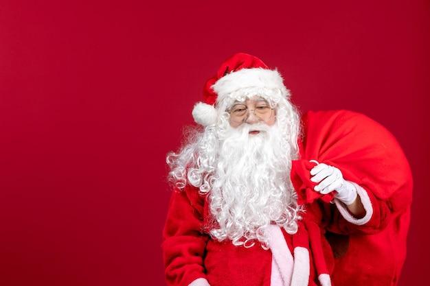 Vooraanzicht kerstman draagtas vol cadeautjes op rode emotie feestdagen nieuwjaar