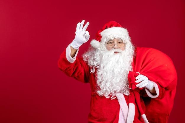 Vooraanzicht kerstman draagtas vol cadeautjes op rode emotie nieuwjaar kerst
