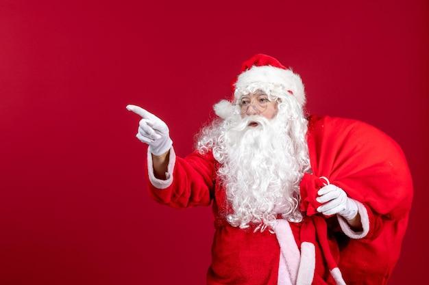 Vooraanzicht kerstman draagtas vol cadeautjes op rode emotie nieuwjaar kerstvakantie mens
