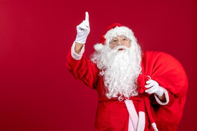 Vooraanzicht kerstman draagtas vol cadeautjes op rode emotie nieuwjaar kerstvakantie