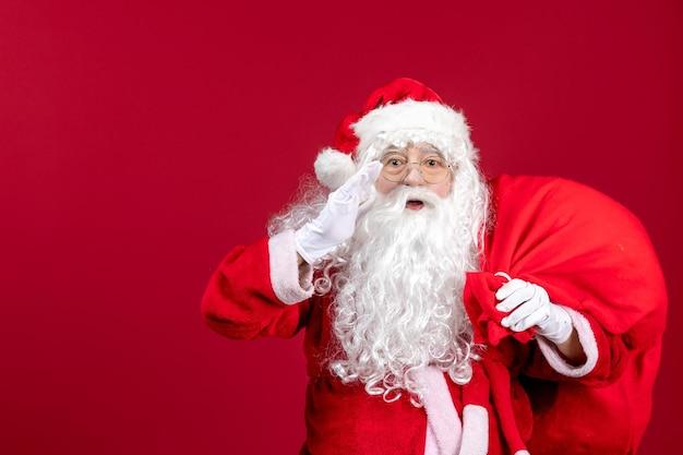 Vooraanzicht kerstman draagtas vol cadeautjes op rode emotie vakantie kerstmis