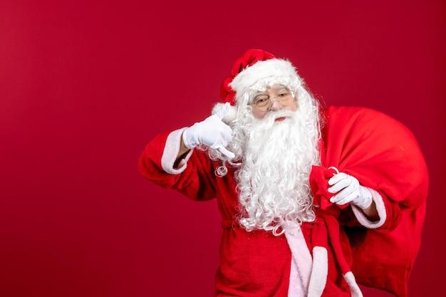 Vooraanzicht kerstman draagtas vol cadeautjes op rode emoties nieuwjaar kerstvakantie