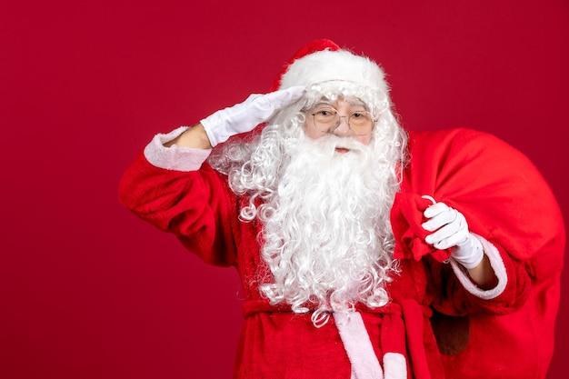 Vooraanzicht kerstman draagtas vol cadeautjes op rode emoties vakantie nieuwjaar kerstmis