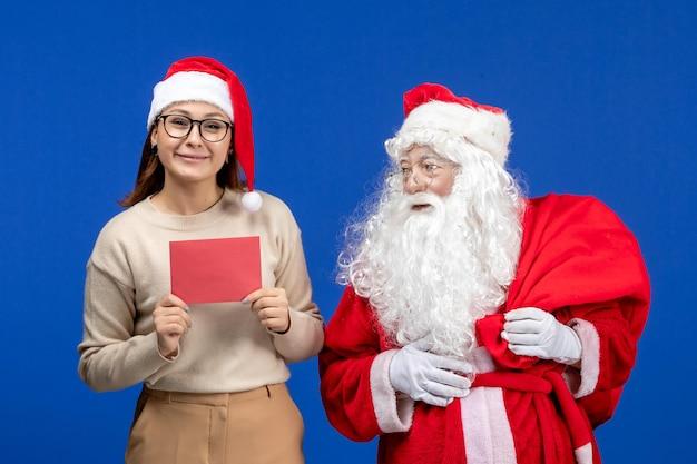 Vooraanzicht kerstman en jonge vrouw met brief op blauwe vakantiegeest emotie kerstsneeuw