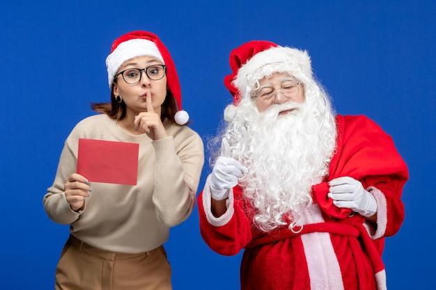 Vooraanzicht kerstman en jonge vrouw met letter op blauwe vakantie emotie kerst nieuwjaar kleur
