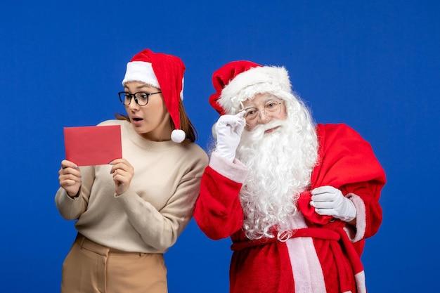 Vooraanzicht kerstman en jonge vrouw met letter op een blauwe vakantie-emotie kerstmis nieuwjaar