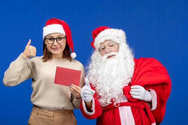 Vooraanzicht kerstman en jonge vrouwelijke houden brief op blauwe vakantie xmas nieuwjaar kleur emoties