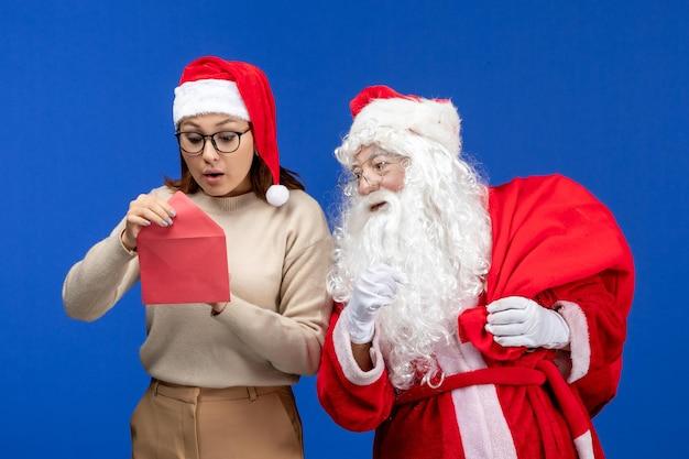 Vooraanzicht kerstman en jonge vrouwelijke openingsbrief op blauwe vakantie-emotie kerstmis nieuwjaar