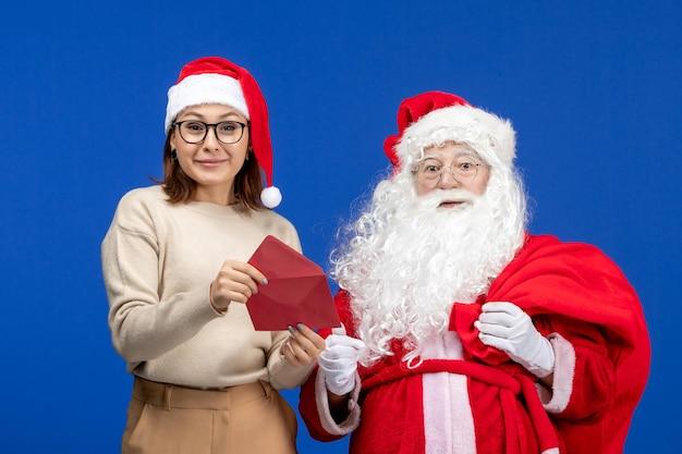 Vooraanzicht kerstman en jonge vrouwelijke openingsbrief op blauwe vakantie kerst nieuwjaar kleur