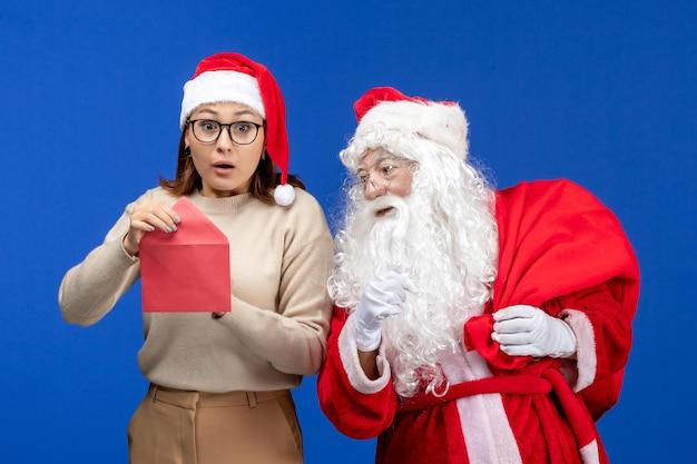 Vooraanzicht kerstman en jonge vrouwelijke openingsbrief op de blauwe vakantie-emotie kerstmis