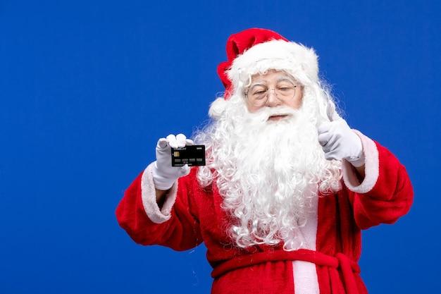 Vooraanzicht kerstman in rood pak met bankkaart op blauw presenteert kerstkleurvakantie
