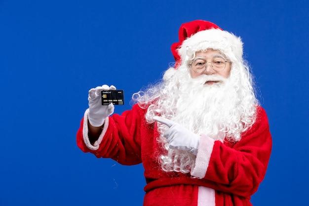 Vooraanzicht kerstman in rood pak met zwarte bankkaart op blauwe presenteert kerstkleurvakantie