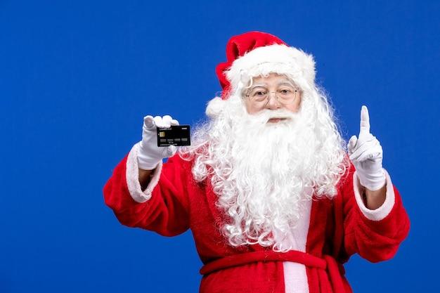 Vooraanzicht kerstman in rood pak met zwarte bankkaart op de blauwe huidige kerstkleurvakantie