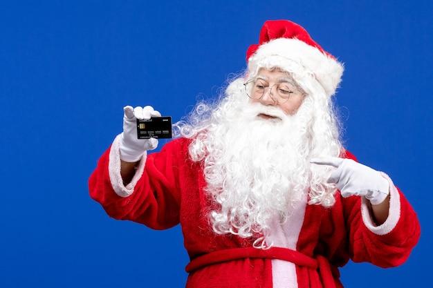 Vooraanzicht kerstman in rood pak met zwarte bankkaart op de blauwe kerstcadeaukleur