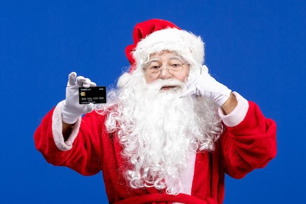 Vooraanzicht kerstman in rood pak met zwarte bankkaart op de blauwe kleur vakantiecadeau xmas