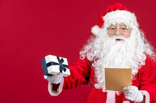 Vooraanzicht kerstman leest brief van kind en houdt aanwezig op rood bureau emotie cadeau kerstvakantie