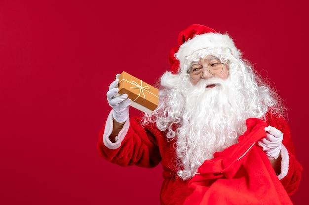 Vooraanzicht kerstman met cadeau uit tas vol cadeautjes voor kinderen op het rode nieuwe jaar