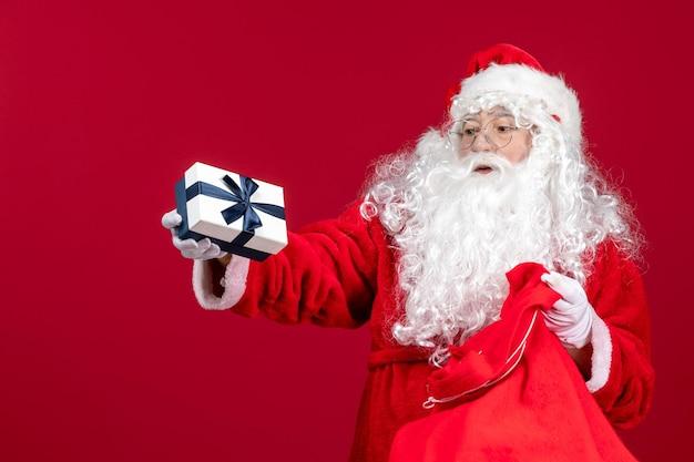 Vooraanzicht kerstman met cadeau uit tas vol cadeautjes voor kinderen op rode nieuwjaarskerstmis