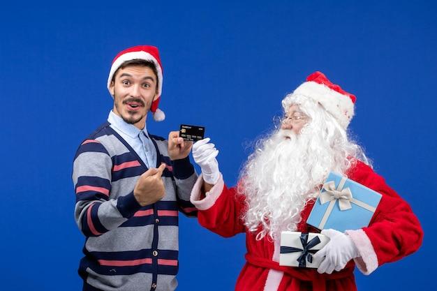 Vooraanzicht kerstman met cadeautjes en jonge man met bankkaart op blauwe kerstemoties