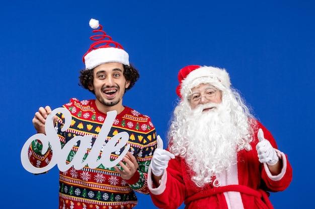 Vooraanzicht kerstman met het jonge mannelijke schrijven van de holdingsverkoop