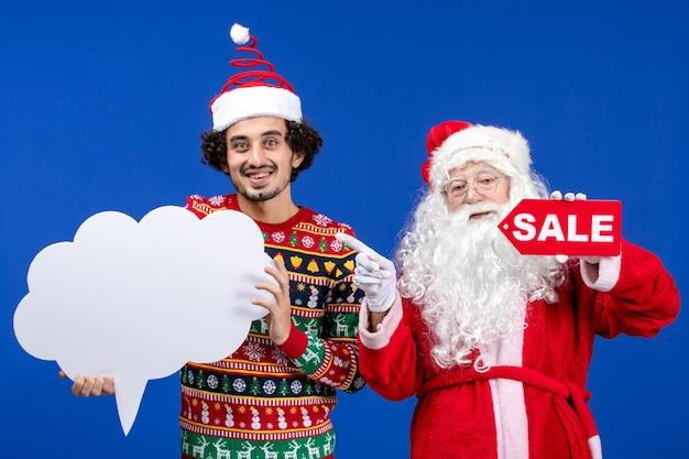 Vooraanzicht kerstman met jong mannetje met wit bord en verkoop schrijven