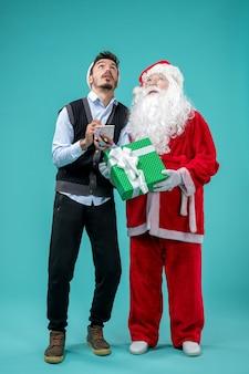 Vooraanzicht kerstman met jonge man die aantekeningen maakt op de blauwe achtergrond