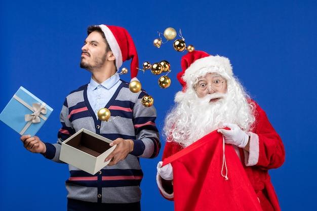 Vooraanzicht kerstman met jonge man en gegooid speelgoed op blauwe kerstvakantie emotie