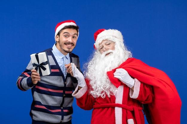 Vooraanzicht kerstman met jonge mannelijke draagtas vol cadeautjes op blauwe emotie vakantie kerstcadeau