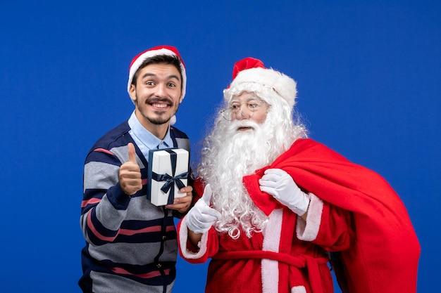 Vooraanzicht kerstman met jonge mannelijke draagtas vol cadeautjes op blauwe emotie vakantie kerstcadeaus