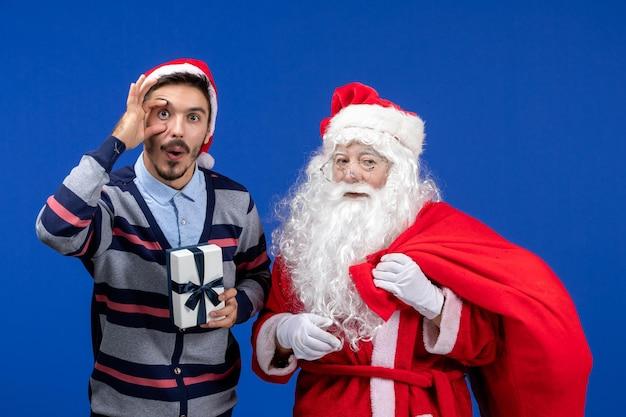 Vooraanzicht kerstman met jonge mannelijke draagtas vol cadeautjes op blauwe kleur vakantiecadeau xmas