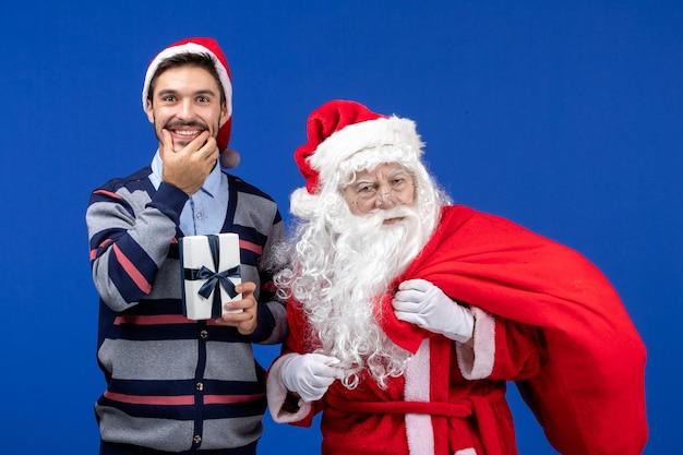 Vooraanzicht kerstman met jonge mannelijke draagtas vol cadeautjes op blauwe kleur vakantiecadeautjes xmas