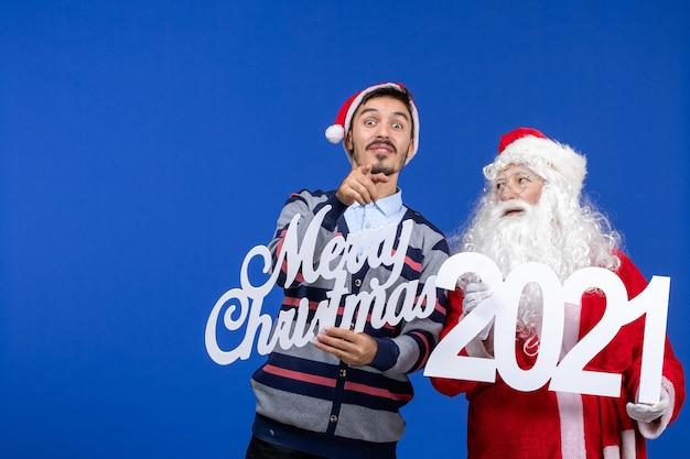 Vooraanzicht kerstman met jonge mannelijke holding en vrolijke kerstgeschriften op blauwe kerstvakantie