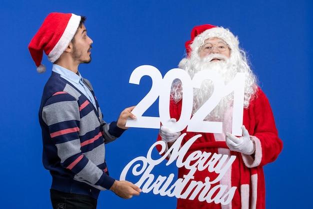 Vooraanzicht kerstman met jonge mannelijke holding en vrolijke kerstgeschriften op het blauwe nieuwe jaar