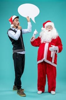 Vooraanzicht kerstman met jonge mannelijke whos die wit teken op de blauwe achtergrond houdt