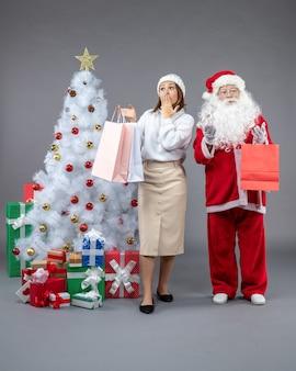 Vooraanzicht kerstman met jonge vrouw rond kerstboom en cadeautjes op de grijze achtergrond