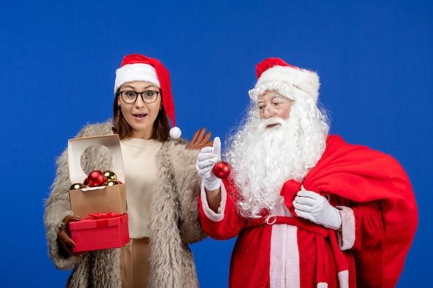 Vooraanzicht kerstman met jonge vrouwelijke handtas met cadeautjes en speelgoed op blauwe feestdagen xmas kleur nieuwjaar