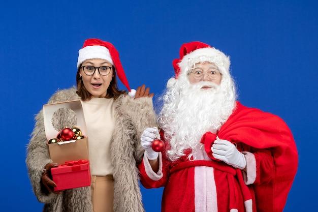 Vooraanzicht kerstman met jonge vrouwelijke handtas met cadeautjes en speelgoed op de blauwe vakantie xmas