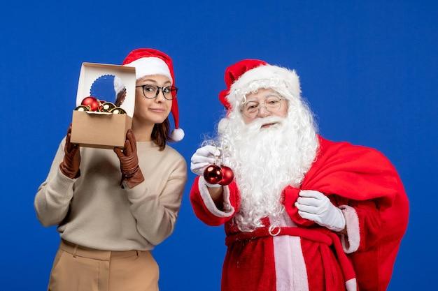 Vooraanzicht kerstman met jonge vrouwelijke handtas met cadeautjes en speelgoed op een blauwe kerstmis nieuwjaarskleur