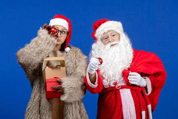 Vooraanzicht kerstman met jonge vrouwelijke holdingstas met cadeautjes en speelgoed op blauwe bureauvakantie