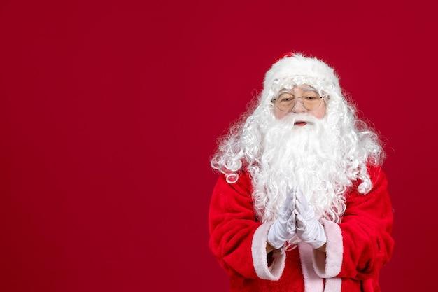 Vooraanzicht kerstman met klassieke witte beer en rode kleren die klappen op rood kerstmis nieuwjaar