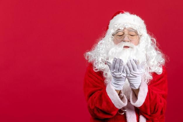 Vooraanzicht kerstman met klassieke witte beer en rode kleren die luchtkussen sturen op rood kerstmis nieuwjaar