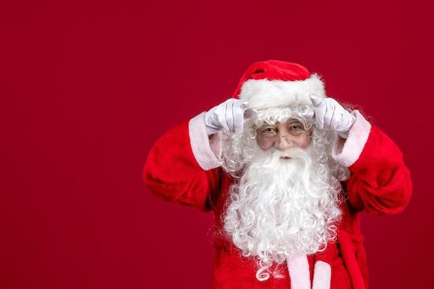 Vooraanzicht kerstman met klassieke witte beer en rode kleren op rood