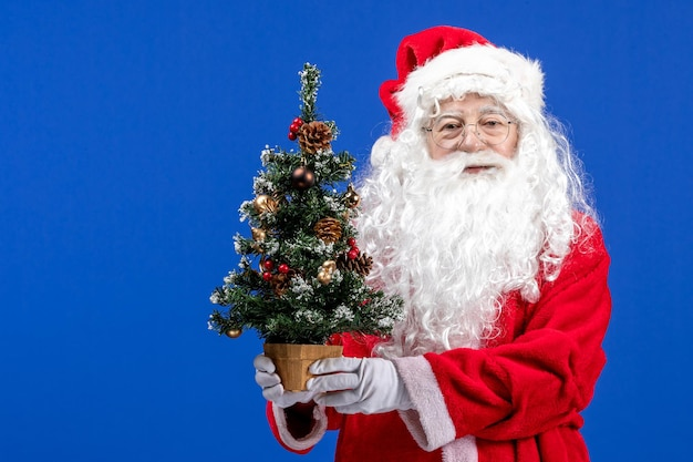 Vooraanzicht kerstman met kleine nieuwjaarsboom op blauw kerstnieuwjaar