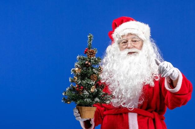 Vooraanzicht kerstman met kleine nieuwjaarsboom op blauwe sneeuwkleur