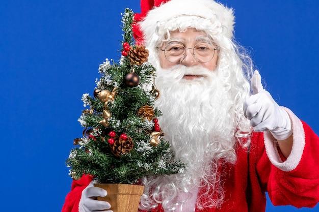 Vooraanzicht kerstman met kleine nieuwjaarsboom op blauwe sneeuwkleuren kerstmis