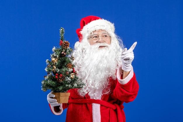 Vooraanzicht kerstman met kleine nieuwjaarsboom op blauwe sneeuwkleuren