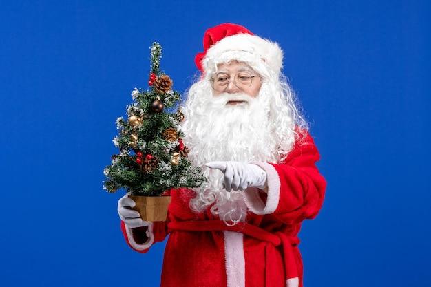 Vooraanzicht kerstman met kleine nieuwjaarsboom op de blauwe sneeuwkleur kerstmis nieuwjaar