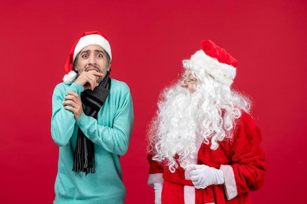 Vooraanzicht kerstman met man die gewoon op de rode huidige vakantie kerstemotie staat